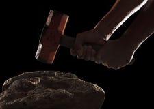 Hand och hammare som bryter på vagga som isoleras på svart Arkivbild