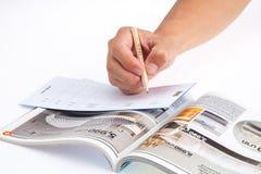 Hand och IKEA katalog Arkivfoton