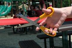 Hand och sax som klipper ett band under en öppningscermoni Arkivfoto