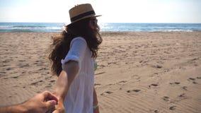 Hand och spring för flicka hållande manlig på stranden till havet Följ som mig, drar skottet av den unga kvinnan i hatt hennes po stock video
