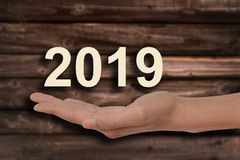 Hand offering 2019 numbers, wood background. Hand offering 2019 numbers, wooden background royalty free stock image