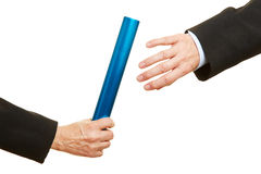 Hand offering and taking relay baton Royalty Free Stock Photo