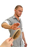 Hand offers hair brush to man Royalty Free Stock Photo