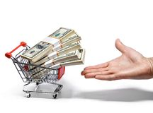 Hand offers shopping cart full of money stacks Royalty Free Stock Photography