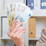 Hand in office holding Euro bills Royalty Free Stock Photography