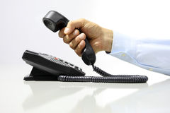 Hand with office phone on desk Stock Image