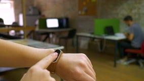 Hand-og das Mädchen gerichtet auf ihr Eignungsarmbandschießen im Büro, das, bewegender Hintergrund Innen versandet stock video