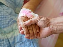 A hand of an old man holding a hand of a sick old lady. A hand of an old man holding a hand of an old lady with intravenous IV catheter on it symbolizing the royalty free stock photo