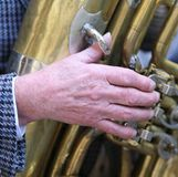 Hand of old man plays the trombone brass stock photo