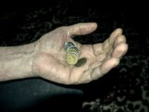 Wrinkled hand holding coins royalty free stock photos