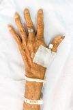 Hand of old patient with plug on bed in hospital Royalty Free Stock Photo