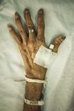 Hand of old patient with plug on bed in hospital Royalty Free Stock Photos