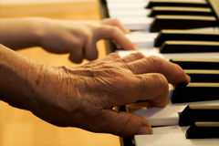 Hand of old piano player and child Royalty Free Stock Photography