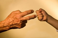 Hand of old woaman and child by game Royalty Free Stock Images