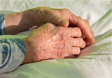 Hand of old woman on the bed Stock Photo