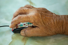 Hand of an old woman holding a computer mouse. Stock Photography