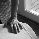 Hand of an old woman ironing. Close up of one hand of an old woman ironing Royalty Free Stock Image