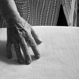 Hand of an old woman ironing. Close up of one hand of an old woman ironing Stock Photos