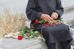 Hand of old woman making bouquet for selling flowers on street Royalty Free Stock Photos