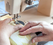 Hand of the old woman at the sewing machine Royalty Free Stock Photo