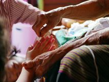 Hands of old woman waving a white string  Sai Sin  around her granddaughter hands - Thai traditional blessing from an elder one royalty free stock images