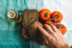 Hand on Olive Oil, tomato and brown bread on tablecloth Royalty Free Stock Photos