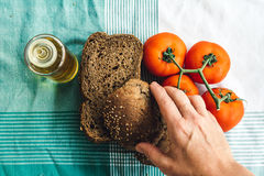 Hand on Olive Oil, tomato and brown bread on tablecloth Stock Photos