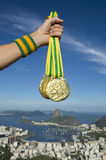 Hand of Olympic Athlete Holding Gold Medals Rio Skyline Stock Photo