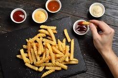 Hand onderdompelende frieten in saus Stock Foto's