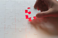 Hand is one last piece of the puzzle Stock Image
