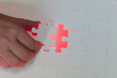 Hand is one last piece of the puzzle Stock Photography