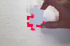 Hand is one last piece of the puzzle Royalty Free Stock Image