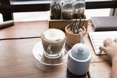 hand op computertoetsenbord met koffiekop Royalty-vrije Stock Foto's