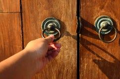 Hand op een handvat houten deur stock foto
