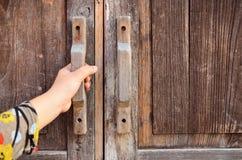 Hand op een handvat houten deur stock afbeeldingen