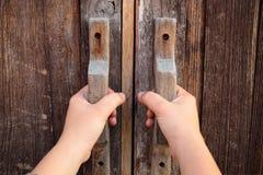 Hand op een handvat houten deur stock afbeelding