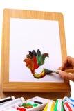 Hand op een schildersezel wordt geschilderd die Royalty-vrije Stock Afbeeldingen