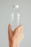 Hand op fles met grijze achtergrond Stock Fotografie