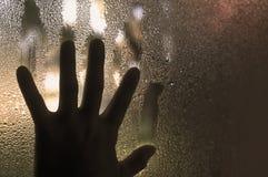 Hand op gecondenseerd nat venster stock afbeelding