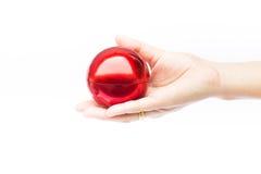 Hand op glanzende rode bal op witte achtergrond Royalty-vrije Stock Foto's