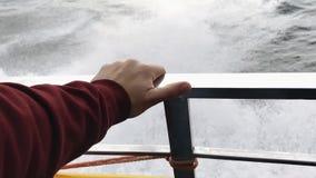 Hand op het traliewerk van een jacht tegen de achtergrond van zeewater stock video