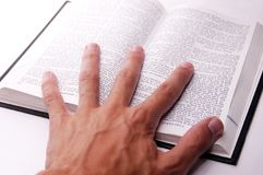 Hand on open book Stock Image