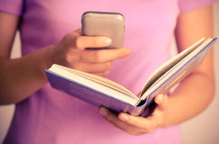 Hand open book ans smart phone. Close up of woman using smart phone for search on book royalty free stock photography
