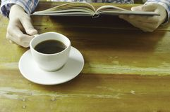 Hand open book and read while drinking black coffee. Cup Stock Image