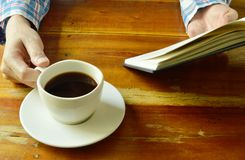 Hand open book and read while drinking black coffee. Cup Royalty Free Stock Photos