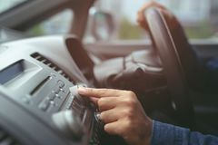 Hand open car radio listening. Car Driver changing turning button Radio Stations on His Vehicle Multimedia System. Close up hand open car radio listening. Car stock image
