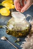 Hand open deksel van ketel met aftreksel van pepermunt gekookt h stock fotografie
