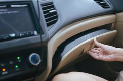 Hand open glove compartment box inside modern car. Hand woman open glove compartment box inside modern car stock images