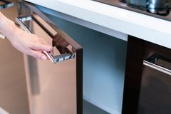 Hand Open Kitchen Cabinet. Close up of hand Open Kitchen Cabinet royalty free stock photography
