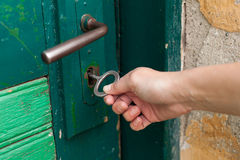 Hand open old door with old key Stock Photography